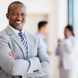 successful african business man with arms folded in modern office
